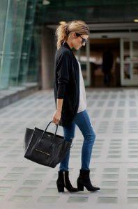 Девушка на улице в черном кардигане, с черной сумкой и в синих джинсах