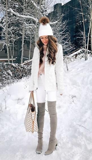 Модель на улице зимой в пуховике до колена, с сумкой в руках, шапке светлого оттенка