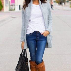 Девушка в серой кофте, коричневых сапогах и с сумкой в руках