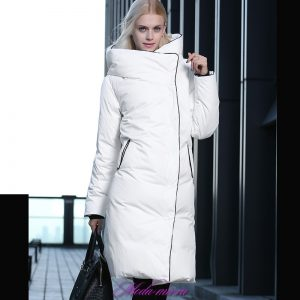 Модель на подиуме в длинном белом пуховике и с черной сумкой в руках