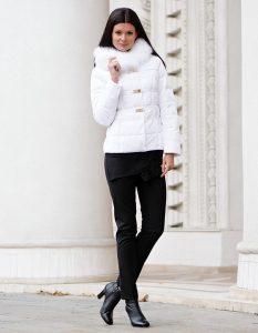 Девушка около белой колонные в коротком белом пуховике, черных брюках