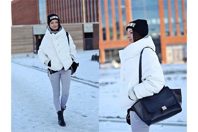 Девушка в коротком пуховике, светлых брюках, черной шапке и с черной сумкой через плечо