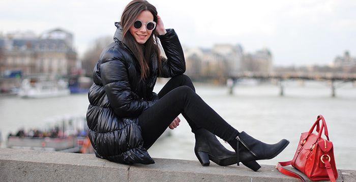 Модель, сидящая на бетонной стене в черном луке