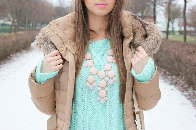 Девушка зимой в бежевом пуховике и салатном свитере