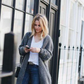 Девушка с телефоном в руках в сером кардигане темного цвета