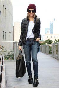 Модель в легком черном пуховике, в белой футболке и джинсах синего цвета