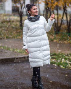 Девушка в широком белом пуховике на осенней улице