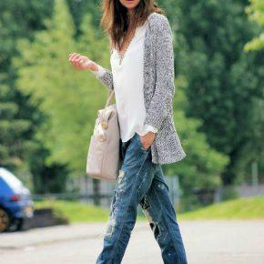 Девушка в сером кардигане, в джинсах, белой блузке и с сумкой в руках