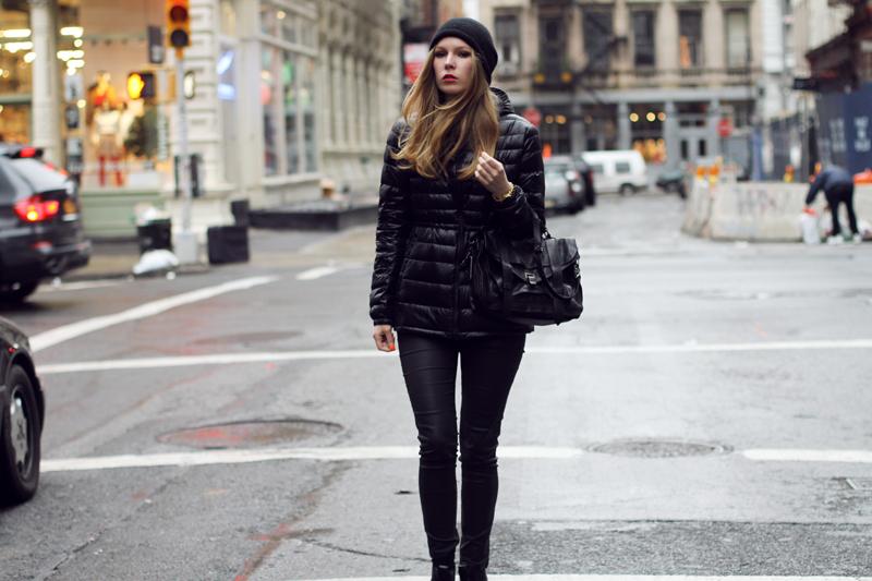 Модель, идущая по улице в черном луке
