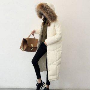 Длинный пуховик светлого оттенка, черные джинсы, коричневая сумка