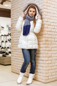 Девушка около кирпичной стены в светлом пуховике