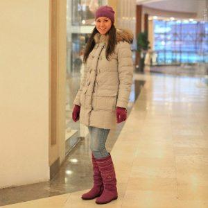 Девушка в торговом центре в ярких сапогах и варежках