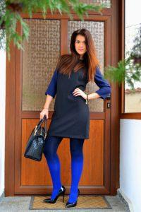 Девушка на улице в градиентных колготах, черном платье, синей блузке и с сумкой в руках