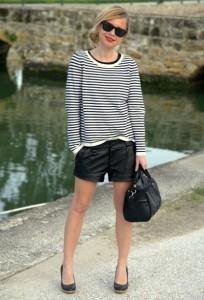 Девушка в свободной полосатой кофте, в черных солнцезащитных очках и в шортах черного цвета