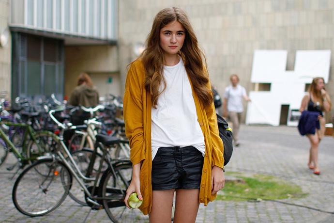 Девушка в горчичном кардигане и кожаных шортах около велосипедов