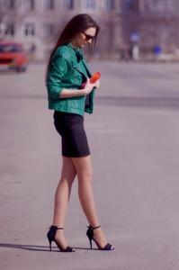 Модель в черном платье и в кожаной короткой куртке