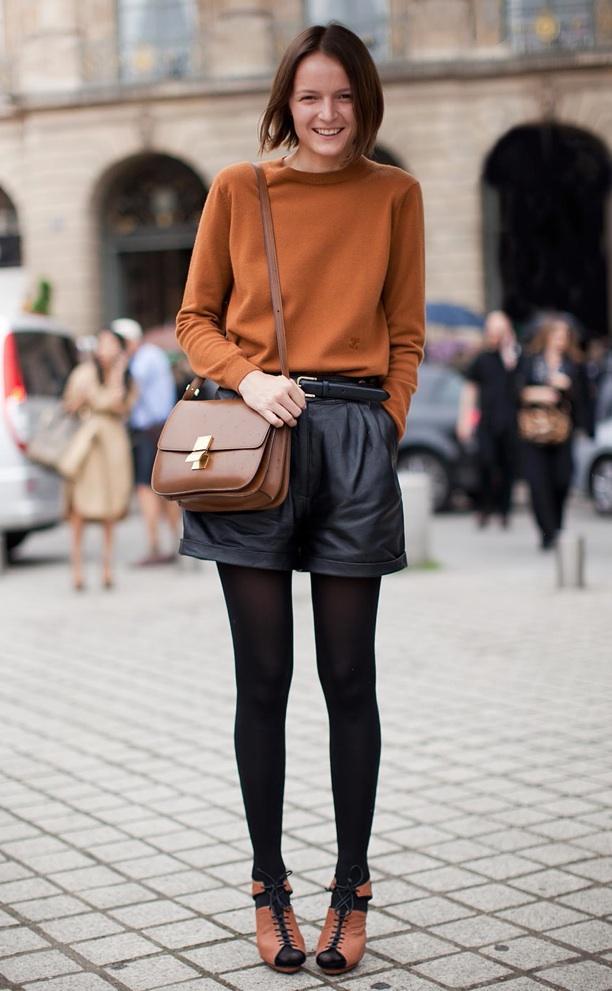 Девушка в коричневом свитере, коричневой сумкой на плече и в шортах