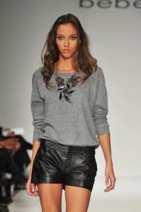 Модель на подиуме в серой кофте и в кожаных шортах черного цвета
