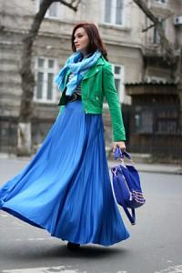 Модель в длинной синей юбке, зеленой кожаной куртке с большой сумкой синего цвета в руке