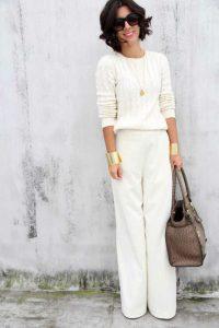 Девушка в белых брюках и светлом свитере с коричневой сумкой в руках