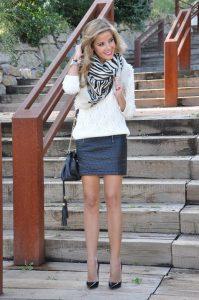 Девушка около ступенек в кожаной юбке и в белом свитере