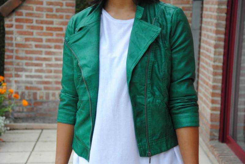 Модель на фоне красной стены в зеленой кожаной куртке