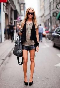 Девушка в коротких шортах, с сумкой на руке, очках, в серой футболке