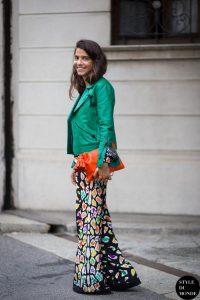 Девушка в длинной цветастой юбке, с яркой оранжевой сумкой и в темно-зеленой куртке
