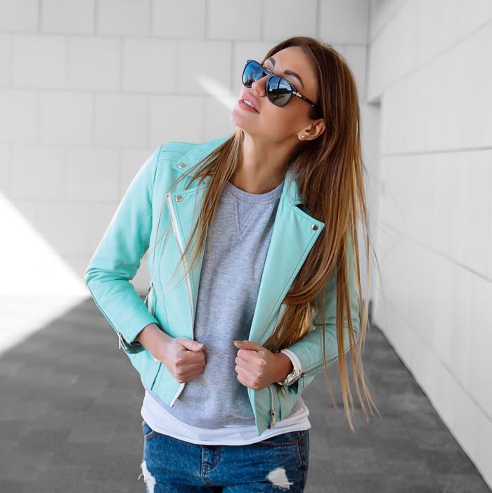 Модель в солнцезащитных очках, кожаной куртке и джинсах темно-синего цвета