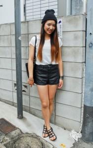 Девушка в кожаных шортах, белой футболке и в темной шапке