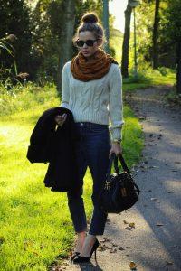 Девушка на улице в джинсах и белом свитере с сумкой черного цвета в руках