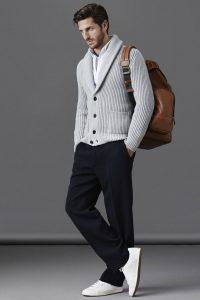 Парень в черных брюках, сером кардигане и с сумкой на плече коричневого цвета