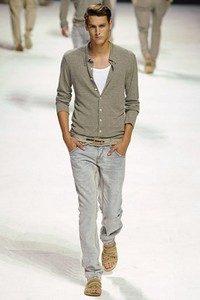 На подиуме молодой человек в джинсах светлого цвета, бежевом кардигане и белой футболке