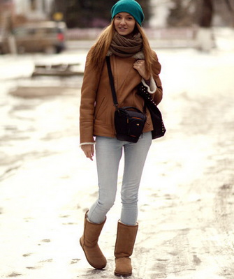 Девушка зимой на улице в коричневых уггах и зеленой шапке