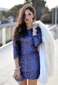 Девушка в синем платье из пайеток и с пушистым кардиганом в руках