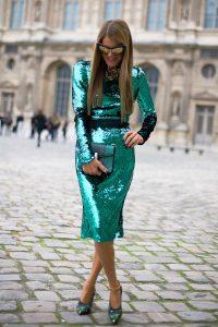 Модель в длинном ярком зеленом платье и с клатчем в руках