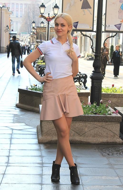 Девушка в юбке и белой футболке поло