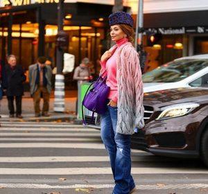Девушка в шапке пилотке на проезжей части в разноцветной кофте