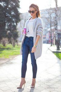 Девушка в белой футболке с башней, джинсах и туфлях на каблуках