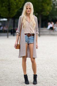 Девушка на улице в длинном кардигане, джинсовых шортах и с сумкой на плече