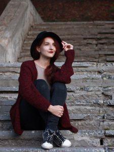 Девушка, сидящая на ступеньках серого цвета