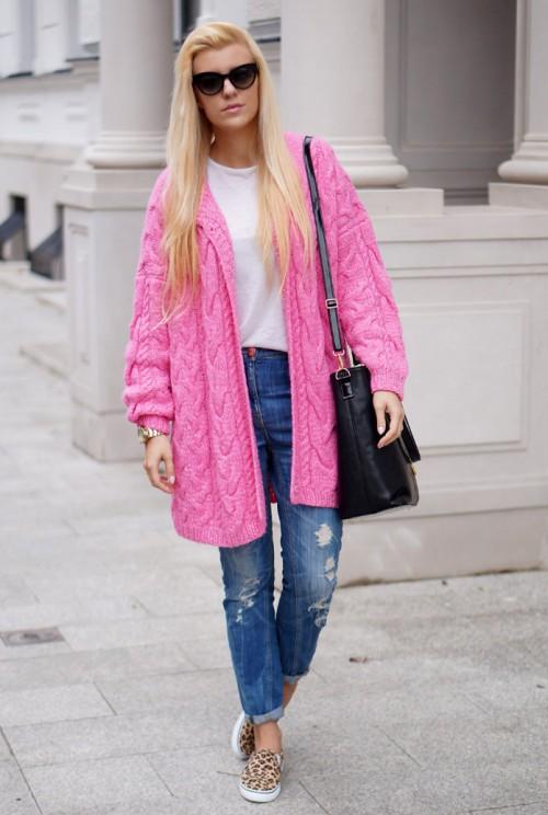 Девушка блондинка в джинсах, ярко розовом кардигане и с черной сумкой на плече