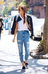 Девушка, идущая по улице в классической белой футболке, кожаной куртке и джинсах светло-голубого оттенка с разрезами