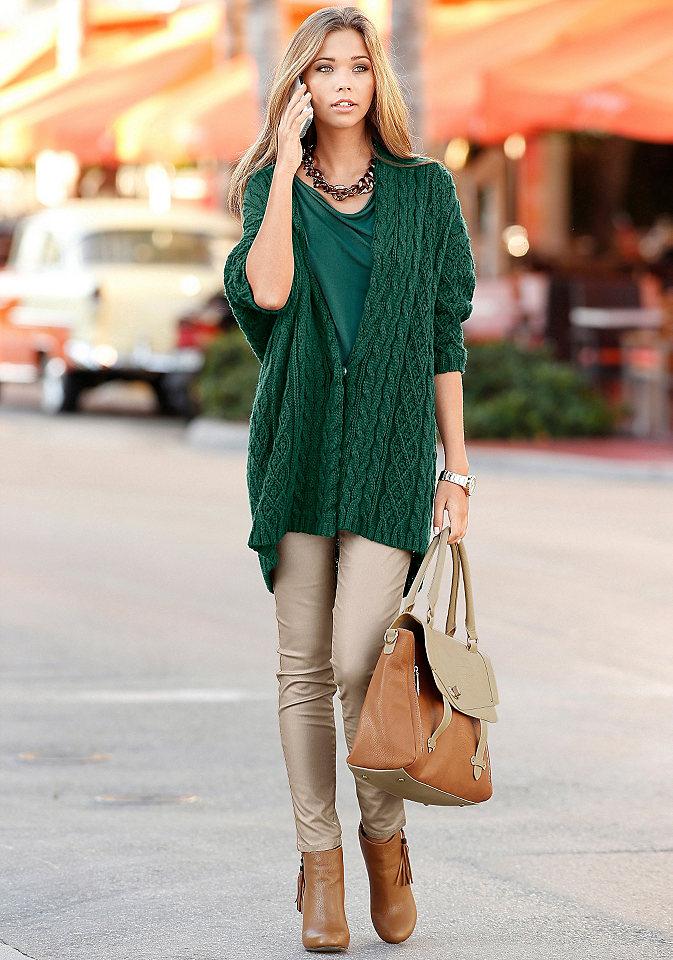Девушка в темно зеленом кардигане с коричневой сумкой в руке