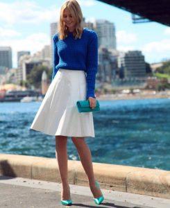 Около пирса девушка в белой юбке и синем свитере