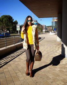 Красивый образ в коричневых брюках, яркой кофте и с сумкой в руках