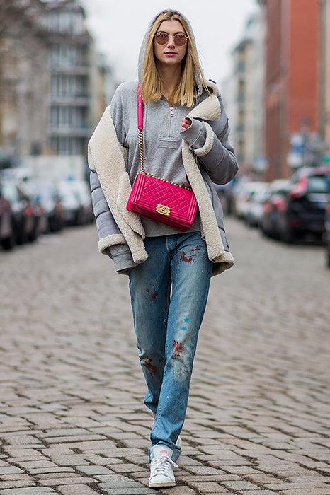 Девушка идущая по улице в худи и с розовой сумкой через плечо
