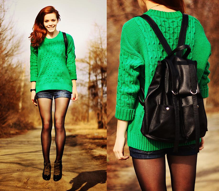 Рыжая девушка в коротких шортах и зеленом свитере