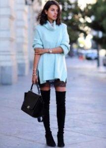 Девушка в голубой длинной кофте и черных ботфортах
