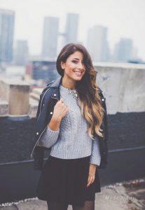 Красива девушка в сером свитере и в черной кожаной кертке